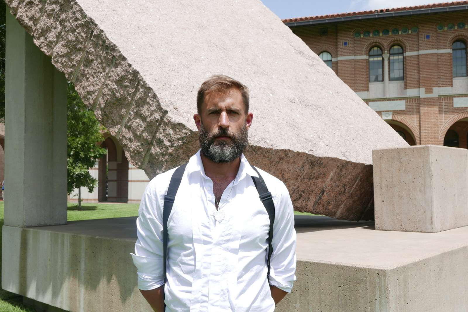 Artist Jarrod Beck with the 45° element of Michael Heizer's massive granite sculpture 45°, 90°, 180° (1984) at Rice University. Photo courtesy Rice Public Art.